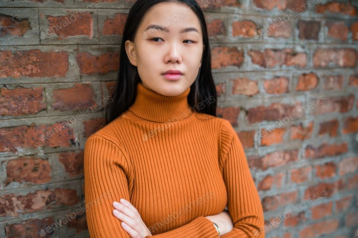 Asian woman against brick wall.