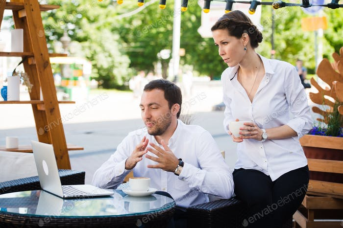 Business Team man and woman at Cafe having a conversation using laptop. Working Meeting Concept