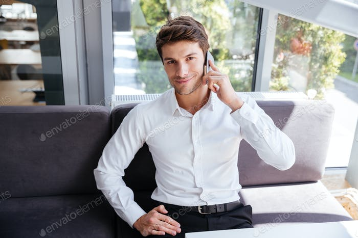 Smiling young businessman talking on mobile phone in office
