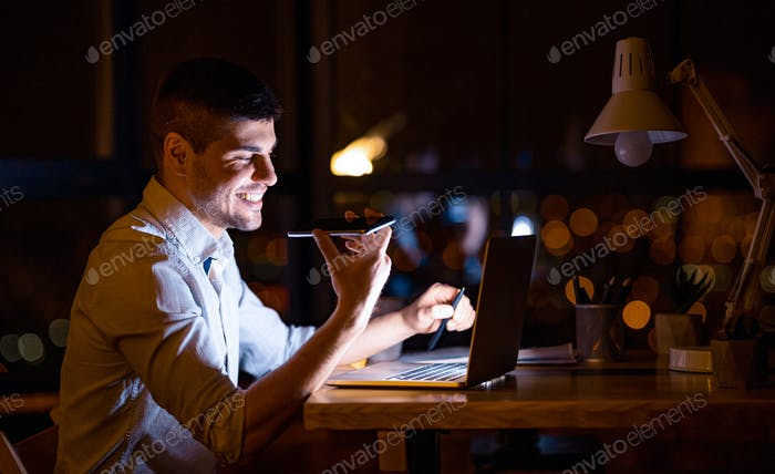 Young Entrepreneur Using Voice Assistant Working On Laptop In Office