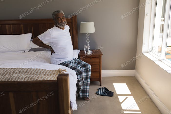 Front view of a senior African American man suffering from back pain in bedroom at home