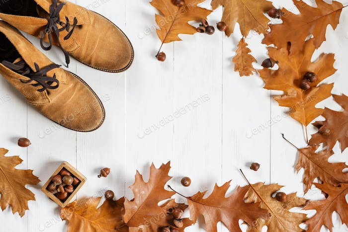 ginger fashion shoes with yellow fallen oak leaves on white wooden background