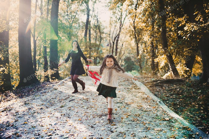 A young mother with a small daughter walking in forest in autumn nature.