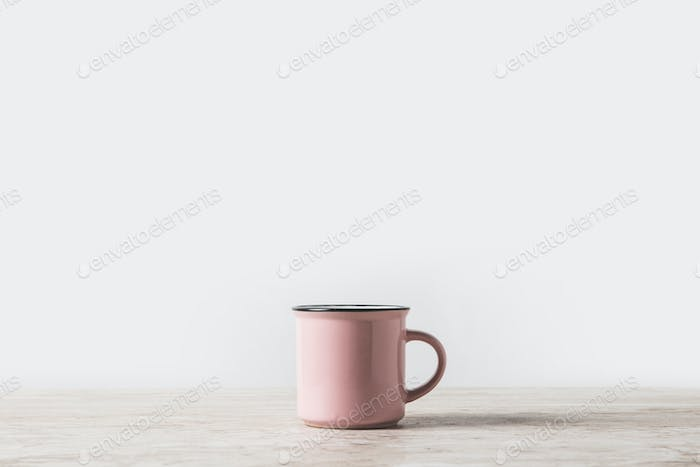 one pink cup on marble table on white
