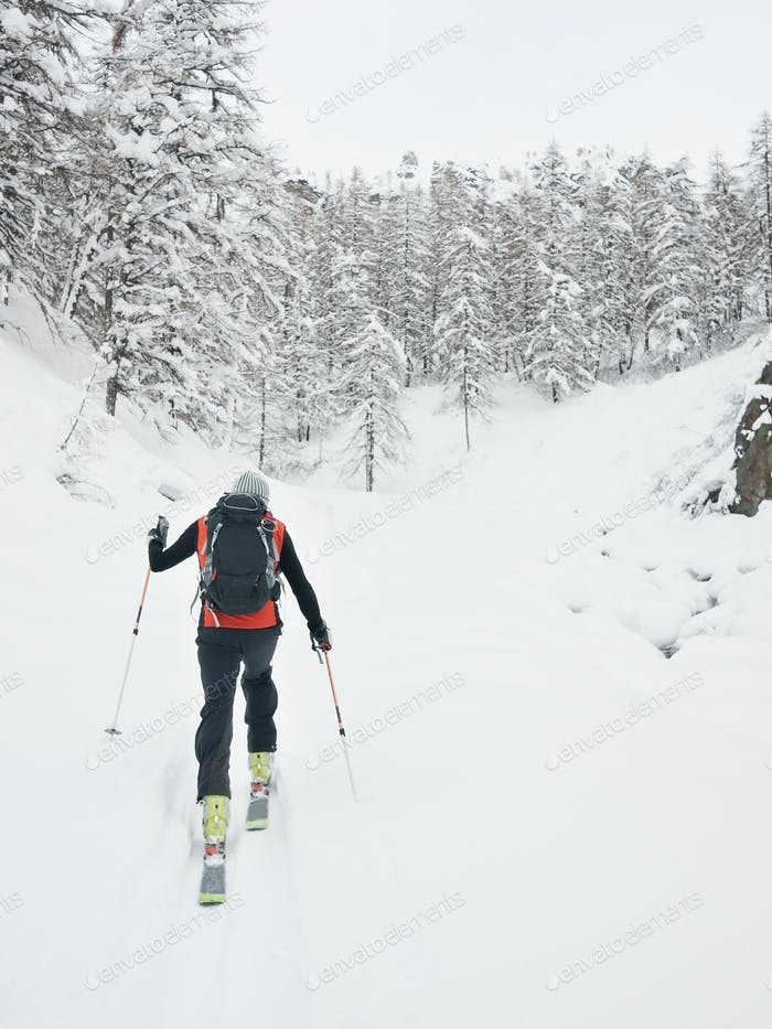 Backcountry skier walks in a snowy mountain valley.