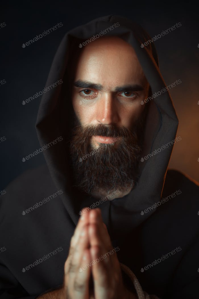 Medieval monk praying with closed eyes