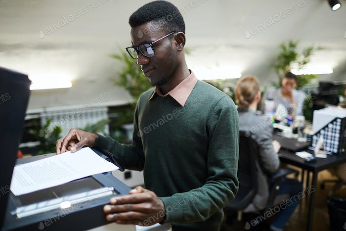 African Intern Using Scanner in Office
