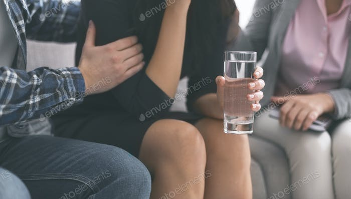 Emotional woman crying with glass of water therapy session