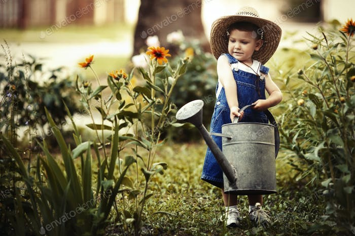 little boy with watering can in summer park