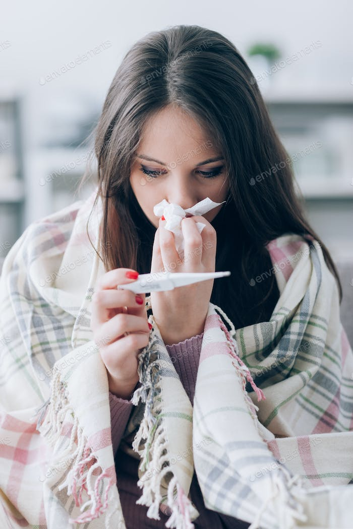 Sick woman taking temperature