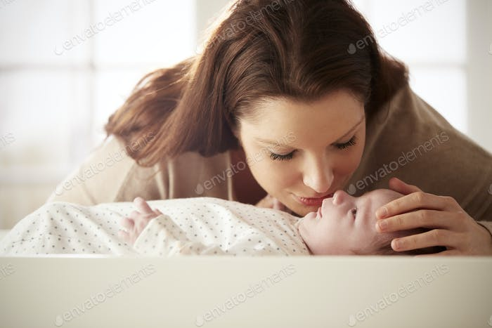 Mother Kissing Newborn Baby Lying On Changing Table In Nursery