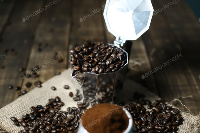 Coffee beans ground coffee in mokapot with wood background