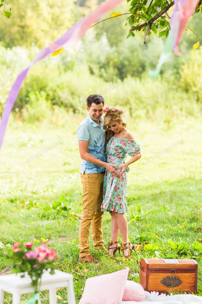 Schönes junges Paar macht Herz der Finger und lächelnd in der Natur