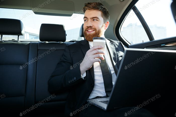 Smiling business man with laptop drinking coffee