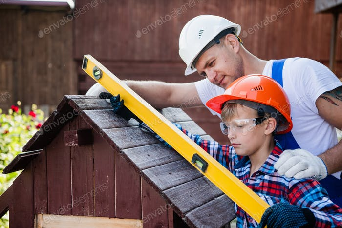 Happy father looking at son measuring wooden plank with building level. Building a dog house at