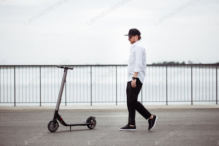Photo of modern man with electric scooter at the street