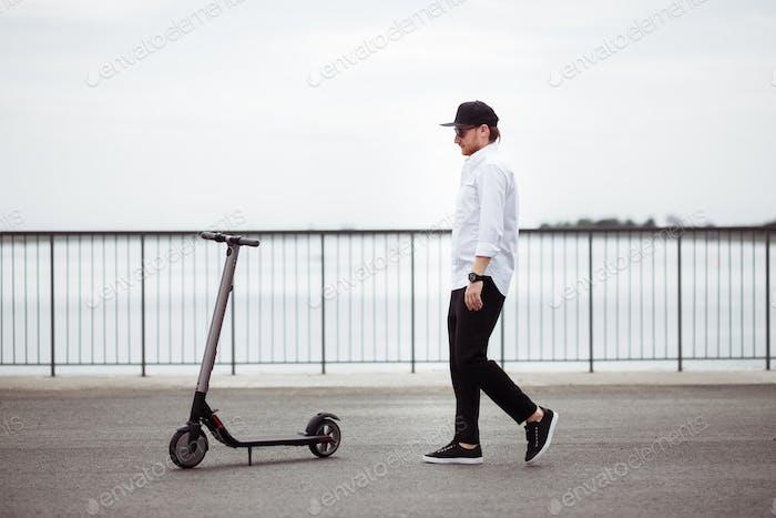 Foto des modernen Mannes mit Elektroroller auf der Straße