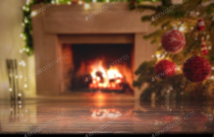 Wooden desk, Christmas tree and burning fireplace background, winter holiday template.