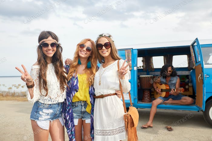 hippie friends near minivan car showing peace sign