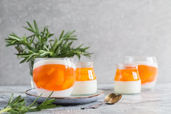 homemade panna cotta with slices of peach and peach jelly in glass jars