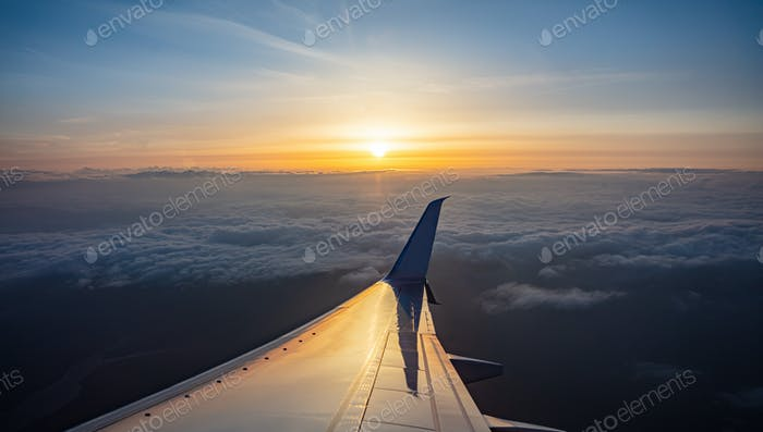 Sunrise view out of an airplane window. Plane flying over the clouds.
