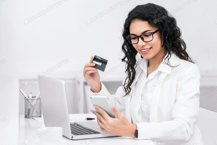 Latin businesswoman booking tickets online using phone