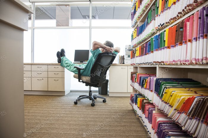 A dentist taking a break with his feet up on a file cabinet.