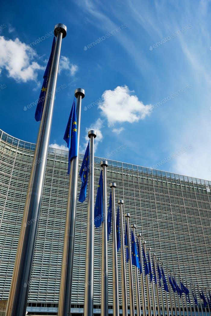 Flaggen der Europäischen Union vor dem Gebäude der Europäischen Kommission im Hintergrund. Brussles, Belgien