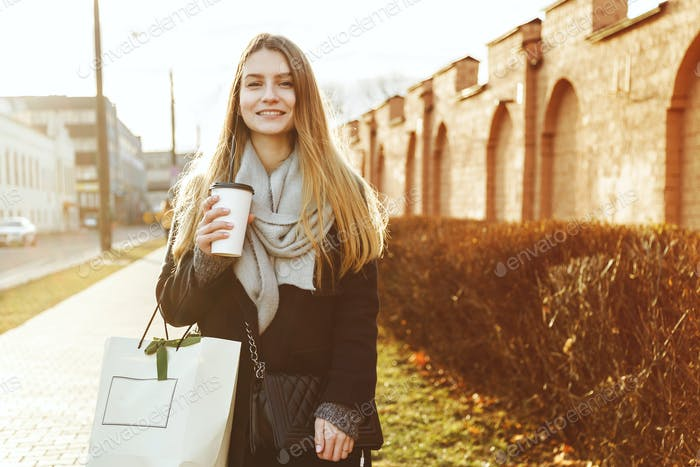 Attractive girl with shopping bags holding disposable cup warm drink.