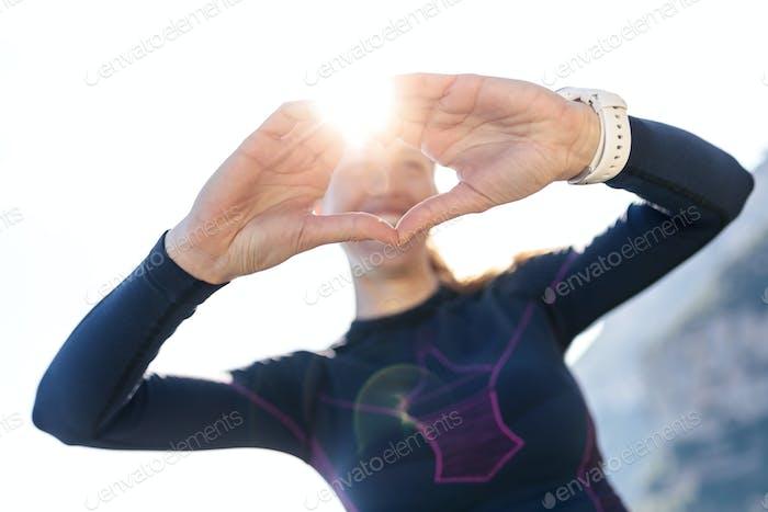 Sportliche junge Frau, die Herzform mit den Händen macht, während sie zu posieren