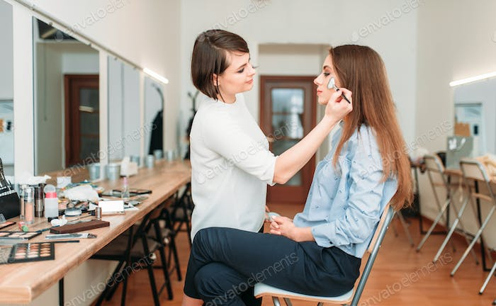 Female make up artist work with woman face