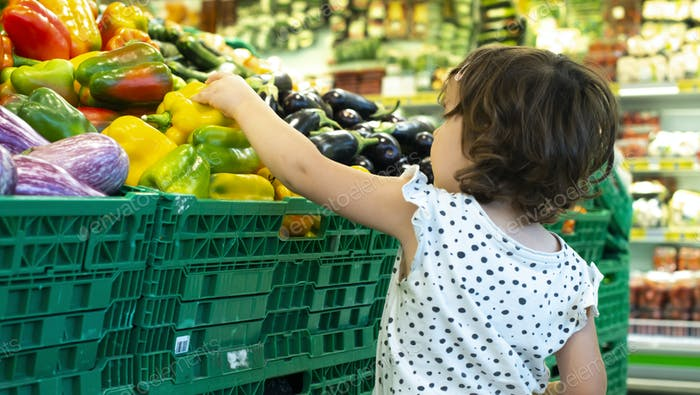 Child shopping peppers in supermarket. Concept for buying fruits