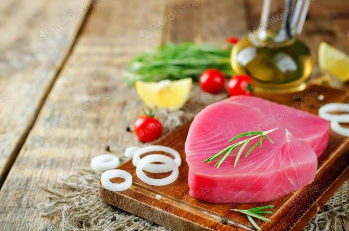 Tuna steak raw with lemon, rosemary, tomatoes and pepper