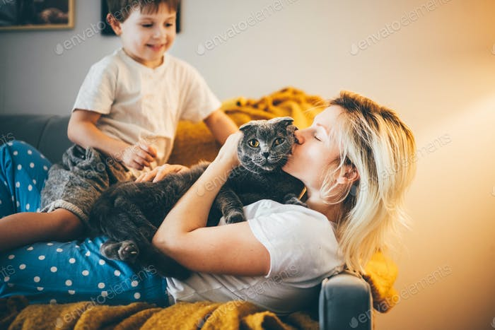Mother and son sitting on floor at home and petting cat.