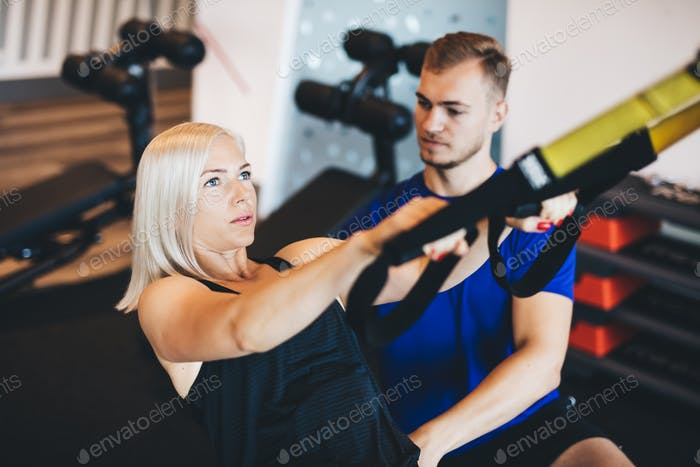 Young woman exercising with personal trainer.