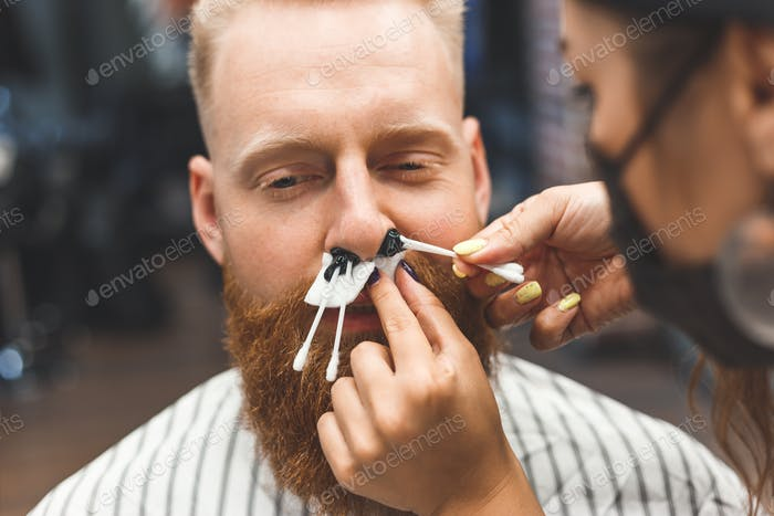 Removing hair from the nose with wax in barbershop, male beauty and care concept