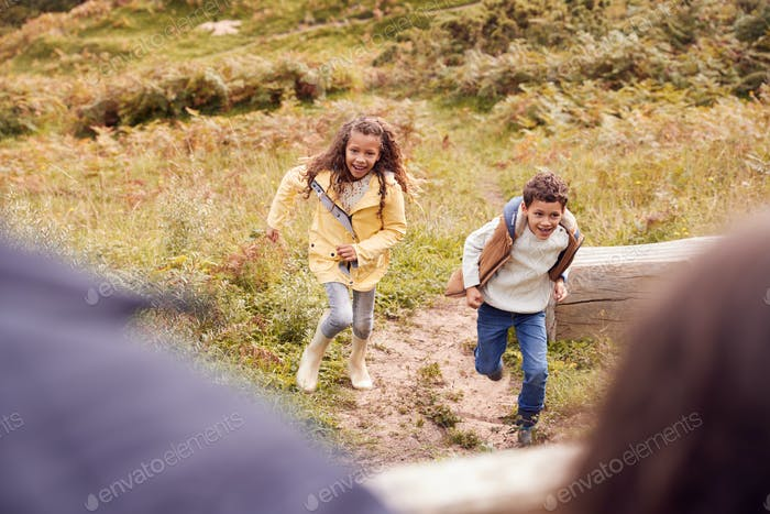 Two Children Running Along Path In Countryside On Winter Vacation