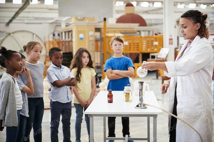 Niños viendo técnico de laboratorio llevar a cabo un experimento Ciencia