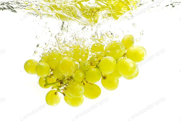 Bunch of green grapes sinking into crystal clear water