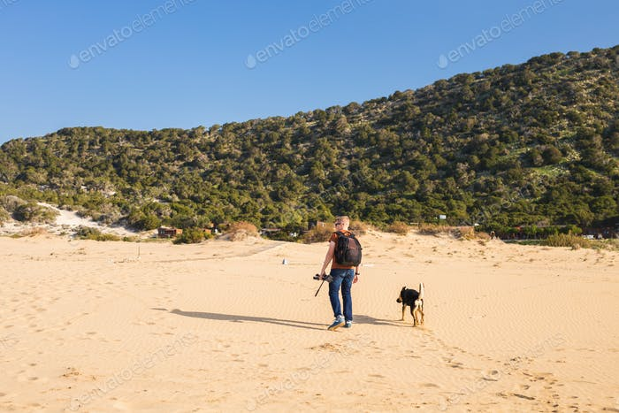 Outdoors lifestyle image of travelling man with cute dog. Tourism concept.