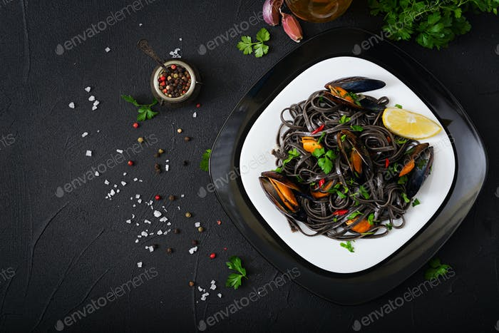 Black spaghetti. Black seafood pasta with mussels over black background