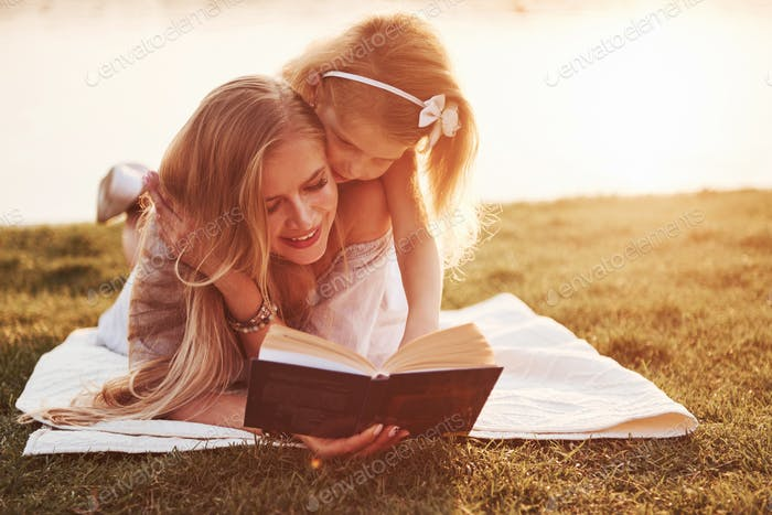 mother with a child reads a book on the grass