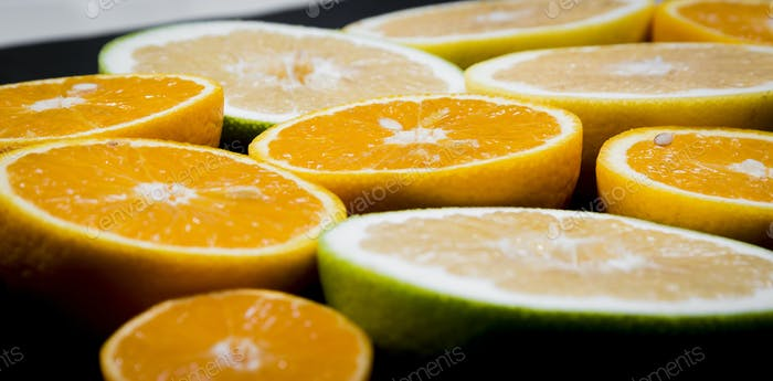 Citrus fruits (orange, lemon, grapefruit, mandarin, lime) on the dark background