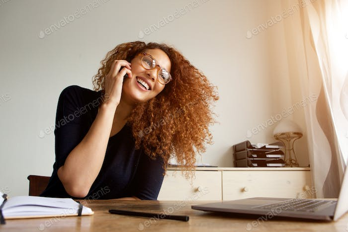 happy young woman talking on cellphone and laughing