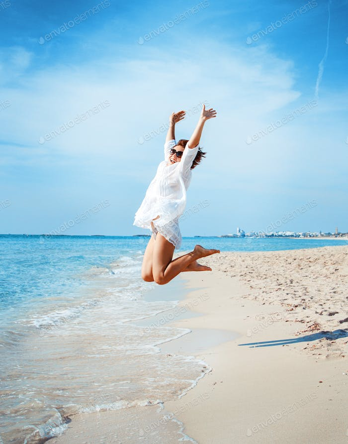 Young woman in cover up  jump on the beach