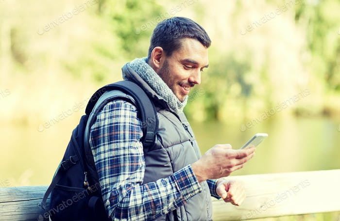 happy man with backpack and smartphone outdoors