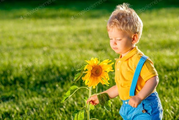 Ein Jahr altes Baby Junge Blick auf Sonnenblume