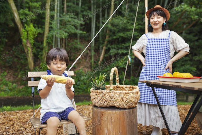 Japanese woman standing outdoors, wearing hat and apron and young boy sitting on chair, eating corn