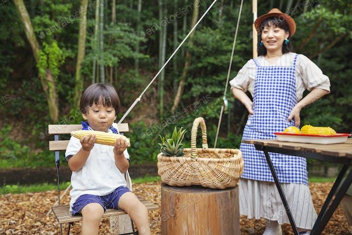 Japanische Frau steht im Freien, trägt Hut und Schürze und kleiner Junge sitzt auf Stuhl, essen Mais