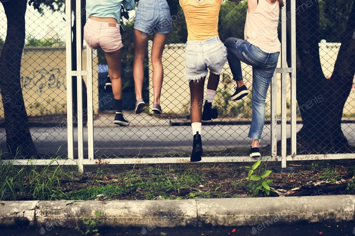 Group of women climbing the fence